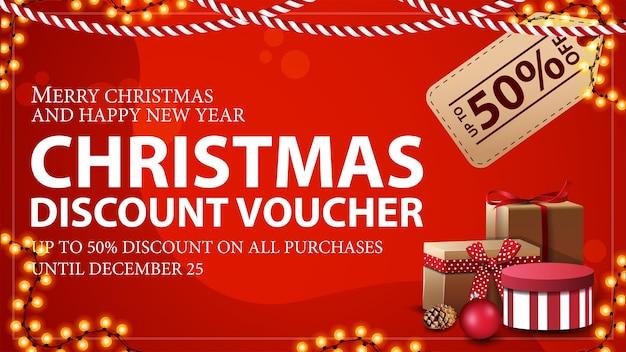 Weihnachtsgutschein mit großem preisschild, geschenken und girlandenrahmen. rabattgutschein, bis zu 50 rabatt auf alle einkäufe.