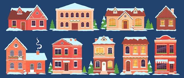 Weihnachtshäuser. gebäude mit schneekappen, die für winterferien mit lichtern, weihnachtsbaum und kranz dekoriert sind. cartoon-stadthäuschen-vektor-set