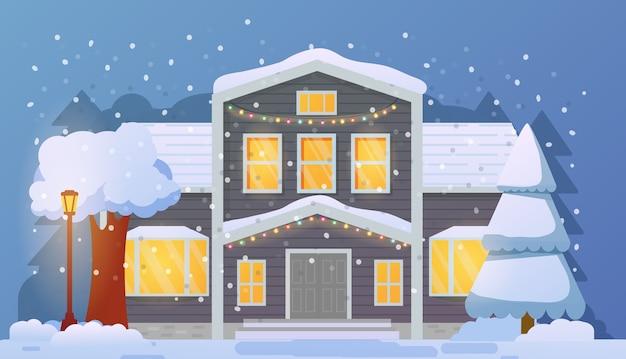 Weihnachtshausfassade im schneefall. frohes neues jahr. ländliches haus im winter.