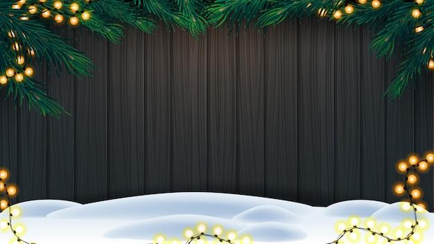 Weihnachtshintergrund, hölzerne wand mit rahmen von weihnachtsbaumasten, girlande und schnee auf boden