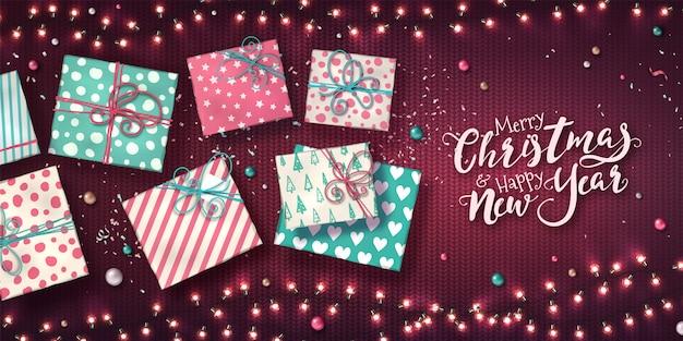 Weihnachtshintergrund mit girlanden von lichtern, von geschenkboxen, von flitter und von konfettis