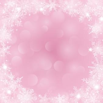 Weihnachtshintergrund mit rahmen aus schneeflocken in form eines kreises in rosa farben und mit bokeh-effekt