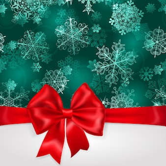 Weihnachtshintergrund mit schneeflocken in türkisfarben und großer roter schleife mit horizontalen bändern