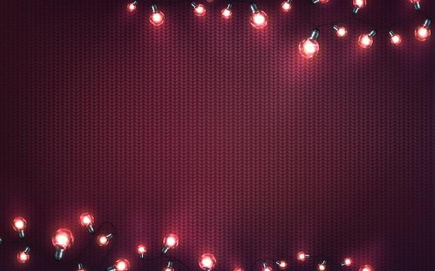 Weihnachtshintergrund mit weihnachtslichtern. glühende girlanden des feiertags von led-glühlampen auf gestrickter beschaffenheit