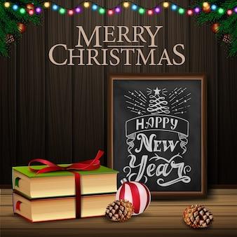 Weihnachtskarte mit tafel und weihnachtsbuch auf hölzernem hintergrund