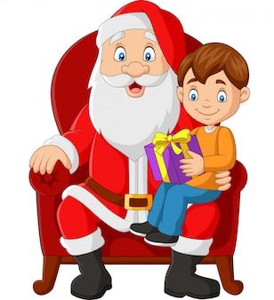 Weihnachtsmann, der im stuhl mit einem kleinen netten jungen sitzt