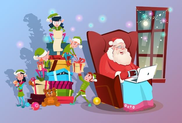 Weihnachtsmann, der laptop-grüne elf-helfer-gruppe verwendet