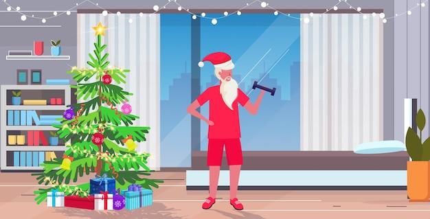 Weihnachtsmann, der mit hanteln trainiert, die gewichte heben bärtiger mann, der trainingskonzept trainiert weihnachten neujahrsfeiertagsfeier modernes wohnzimmer interieur