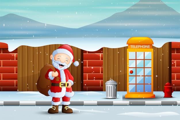 Weihnachtsmann, der mit tasche auf schneebedeckter straße geht
