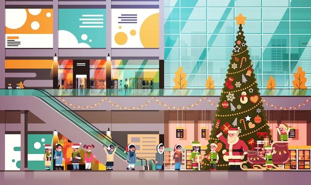 Weihnachtsmann-elfen geben den modernen einzelhandelsgeschäftinnenraum der anwesenden geschenkboxkindergruppe, der für weihnachtsfeiertagskonzeptebene des neuen jahres horizontal verziert wird