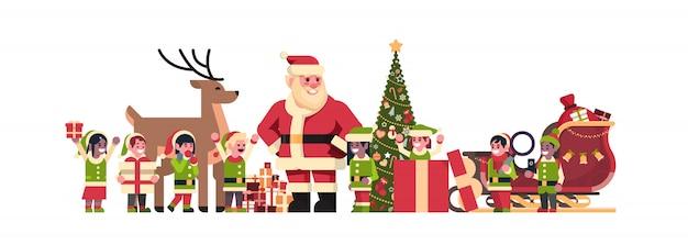 Weihnachtsmann-elfenren nahe tannenbaum-dekorationsgeschenkboxweihnachtsfeiertags-konzeptebene des neuen jahres horizontal lokalisiert