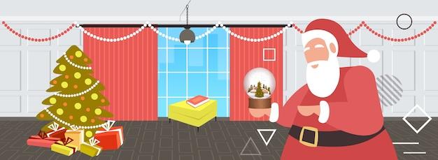 Weihnachtsmann hält magische glaskugel frohe weihnachten frohes neues jahr feiertagsfeierkonzept modernes wohnzimmerinnenraum horizontale porträtvektorillustration