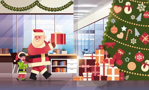 Weihnachtsmann mit dem elfenhelfer, der anwesend unter verzierten tannenbaum in das feiertagskonzept der frohen weihnachten des modernen büros guten rutsch ins neue jahr flach horizontal gesetzt wird
