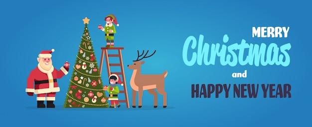 Weihnachtsmann mit elfen auf der treppe schmücken tanne