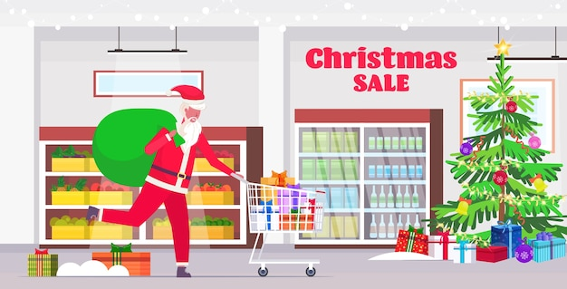 Weihnachtsmann mit großem sack, der wagen mit geschenkgeschenkboxen schiebt weihnachtsverkaufsfeiertagsfeier-einkaufskonzept moderner supermarktinnenraum