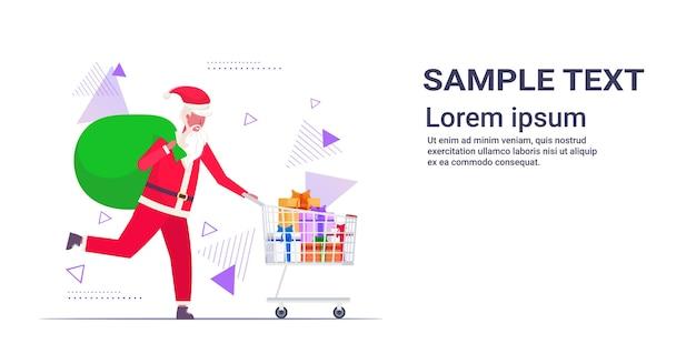 Weihnachtsmann schiebt wagen mit geschenkgeschenkboxen weihnachtsverkauf feiertagsfeier-einkaufskonzept