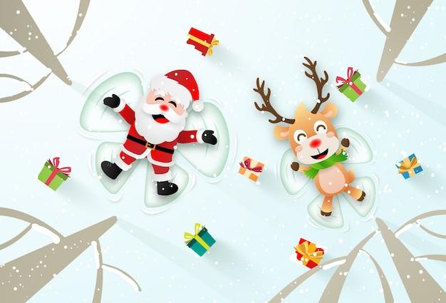 Weihnachtsmann und rentier machen einen schneeengel