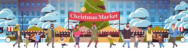 Weihnachtsmarkt oder feiertagsmesse im freien mit dekorierten tannenbaumleuten, die in der nähe von ständen frohe weihnachten neujahrswinterferienfeierkonzept moderner stadtbildhintergrund gehen