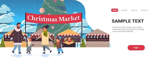 Weihnachtsmarkt oder feiertagsmesse im freien mit geschmückter tannenbaumfamilie, die in der nähe von ständen frohe weihnachten neujahr winterferien feier banner geht