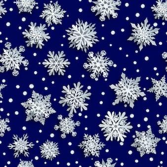 Weihnachtsnahtloses muster aus weißen komplexen papierschneeflocken mit weichen schatten auf dunkelblauem hintergrund