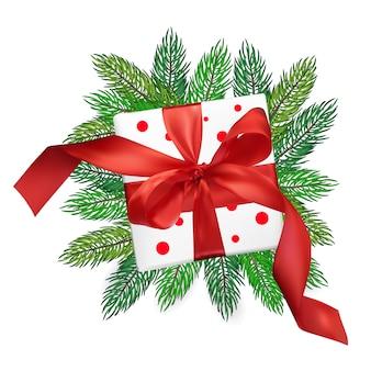 Weihnachtsrealismus-maschengeschenkbox mit einem roten bogen auf weihnachtsbaumasten
