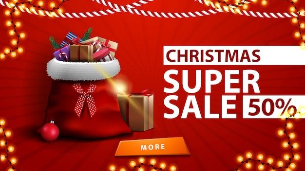 Weihnachtssuperverkauf, bis zu 50% rabatt, rote rabattfahne mit santa claus-tasche mit geschenken nahe der wand