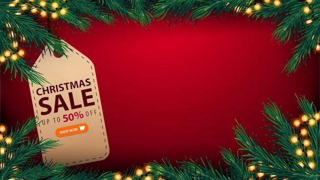 Weihnachtsverkauf, bis zu 50% rabatt, rote vorlage des rabattbanners mit kopierraum, girlandenrahmen, rahmen aus christbaumzweigen und großem preisschild mit angebot und knopf