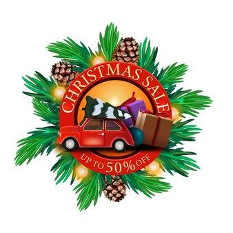 Weihnachtsverkauf, bis zu 50% rabatt, runde rabatt-banner mit weihnachtsbaumzweigen und rotem oldtimer mit weihnachtsbaum