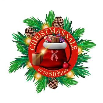 Weihnachtsverkauf, bis zu 50% rabatt, rundes rabatt-banner mit weihnachtsbaumzweigen und weihnachtsmann-tasche mit geschenken