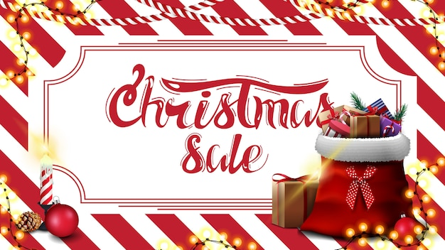 Weihnachtsverkauf, rabattfahne mit roter und weißer gestreifter beschaffenheit auf dem hintergrund und santa claus-tasche mit geschenken