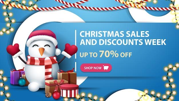Weihnachtsverkauf und rabattwoche, bis zu 70 rabatt, mit dekorativen ringen, girlanden und schneemann in weihnachtsmannmütze mit geschenken