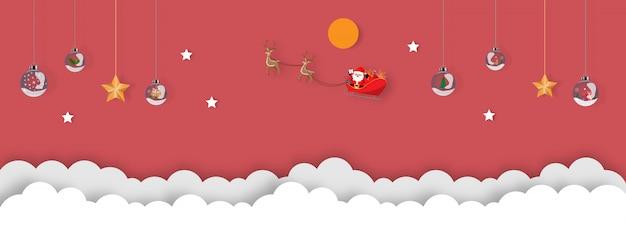 Weihnachtsverzierung, die an der roten hintergrundpapier-schnittart hängt