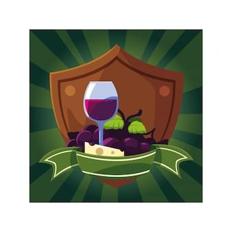 Weinglas mit trauben und käseportion im schild mit band