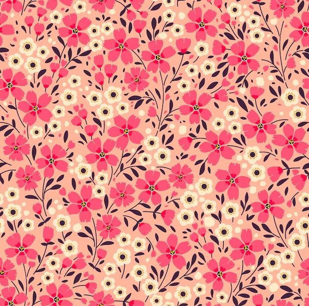 Weinleseblumenhintergrund. nahtloses muster mit kleinen rosa blumen auf einem korallenhintergrund.