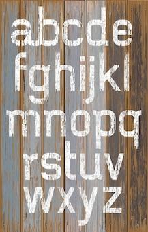 Weiße farbfarbe des alphabets auf retro-farbhintergrund des holzes