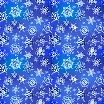 Weiße gefrorene schneeflocken auf blauem winterhintergrund, nahtloses muster