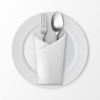 Weiße leere flache runde platte mit silberner gabel und löffel und weißer gefalteter umschlag serviette draufsicht lokalisiert auf weißem hintergrund. sitzordnung bei tisch