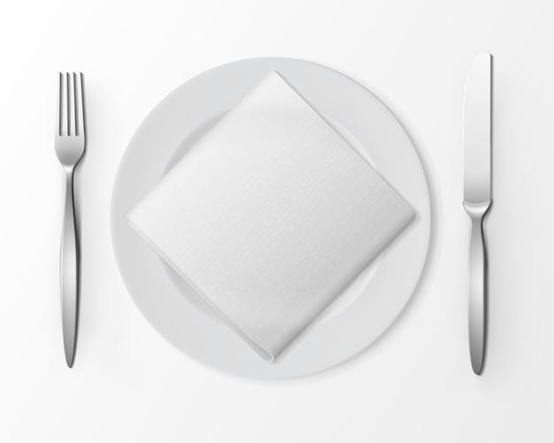 Weiße leere flache runde platte mit silberner gabel und messer und weißer gefalteter quadratischer serviette isoliert, draufsicht auf weiß.