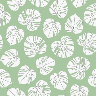 Weiße monstera-blätter auf grünem nahtlosem muster.