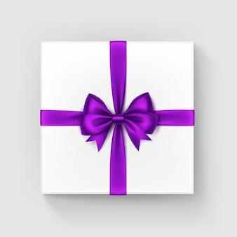 Weiße quadratische geschenkbox mit glänzendem lila band, draufsicht