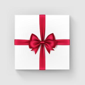 Weiße quadratische geschenkbox mit glänzendem rotem band