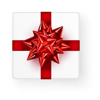 Weiße quadratische geschenkbox mit großer glänzender roter schleifenband-draufsicht lokalisiert auf weißem hintergrund mit schatten.