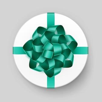 Weiße runde geschenkbox mit glänzend grünem smaragdbogen und band draufsicht nahaufnahme lokalisiert auf hintergrund