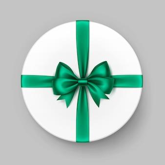 Weiße runde geschenkbox mit glänzend grüner smaragd-satinschleife und band