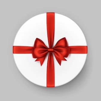 Weiße runde geschenkbox mit glänzend roter satinschleife und band