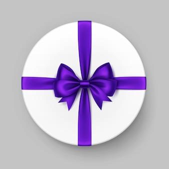 Weiße runde geschenkbox mit glänzendem lila satinbogen und -band