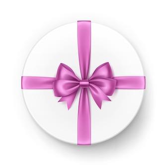 Weiße runde geschenkbox mit glänzender hellrosa satinschleife und band