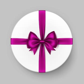 Weiße runde geschenkbox mit glänzender magentafarbener satinschleife und band