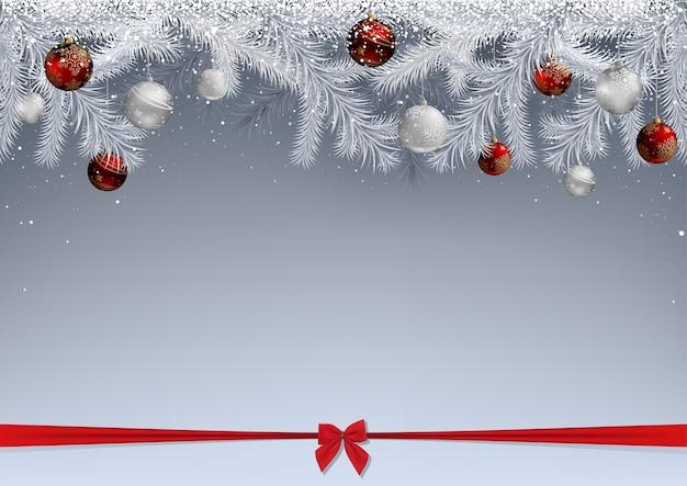 Weiße tannenzweige mit schnee bedeckt und mit kugeln verziert