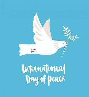 Weiße taube, taube oder vogel fliegen und tragen olivenzweig. schönes symbol der liebe und des pazifismus und der inschrift des internationalen tag des friedens oder der handbeschriftung.